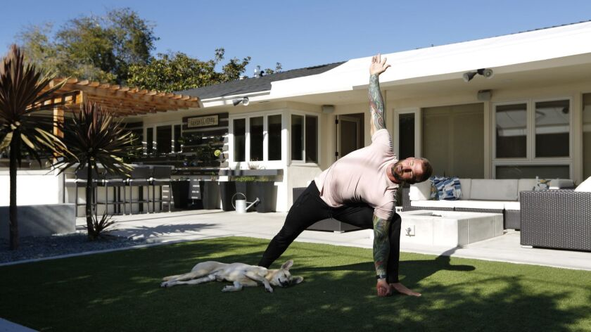 Former San Diego Charger Nick Hardwick does yoga with his dog Dale at his Point Loma home.