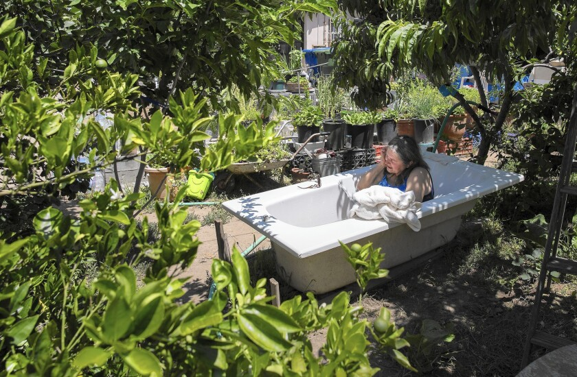 Agneta Dobos, 67, bathes in an outdoor tub on her property in Tujunga.