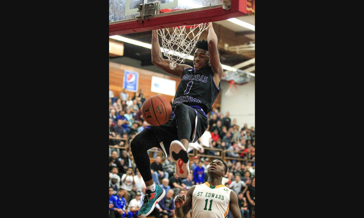 Foothills Christian's Jaylen Hands dunks the ball as St. Edward's Demetrius Terry watches during the first half.