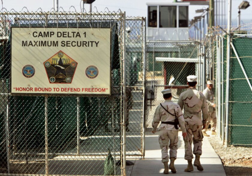 In this 2006 file photo, guards walk inside the U.S. military prison at Guantanamo Bay, Cuba, where most of the 166 prisoners have been on hunger strikes for months.