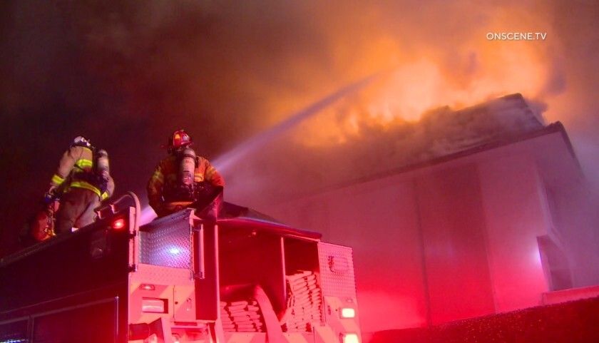 Firefighters spray water onto the flames erupting from the roof of one of the buildings at the Del Mar Beach Club in Solana Beach on Tuesday night.