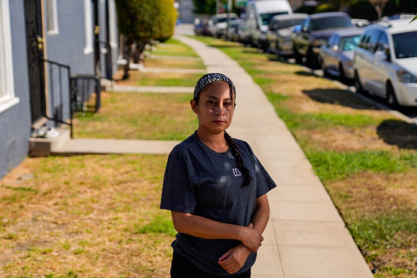 McDonald's worker Lizzet Aguilar poses for a portrait outside while wearing a T-shirt with the McDonald's logo