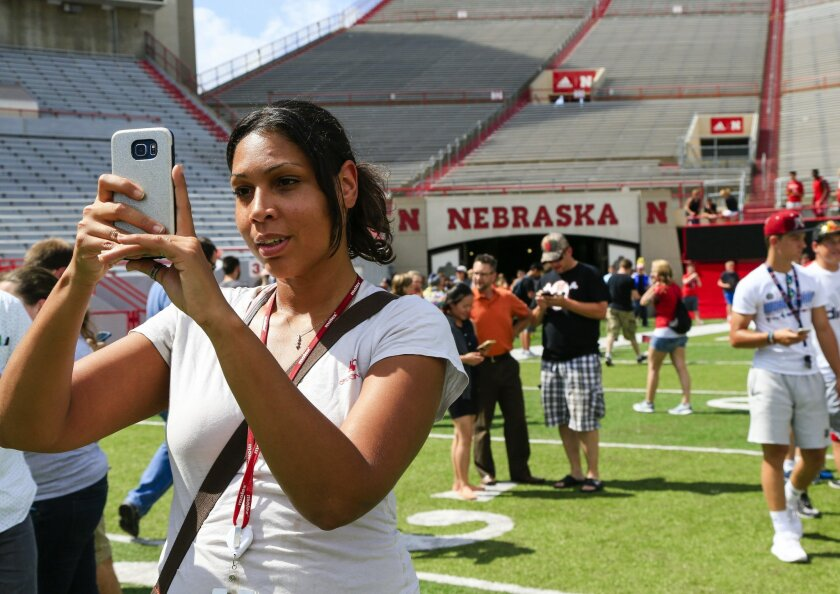 """Nicole Warbelton plays during a """"Pokemon Go"""" event at Memorial Stadium in Lincoln, Neb., Thursday, July 14, 2016. Nebraska Athletic Department officials opened Memorial Stadium for two hours Thursday to accommodate """"Pokemon Go"""" players eager to capture animated monsters at the venerated field. (AP Photo/Nati Harnik)"""
