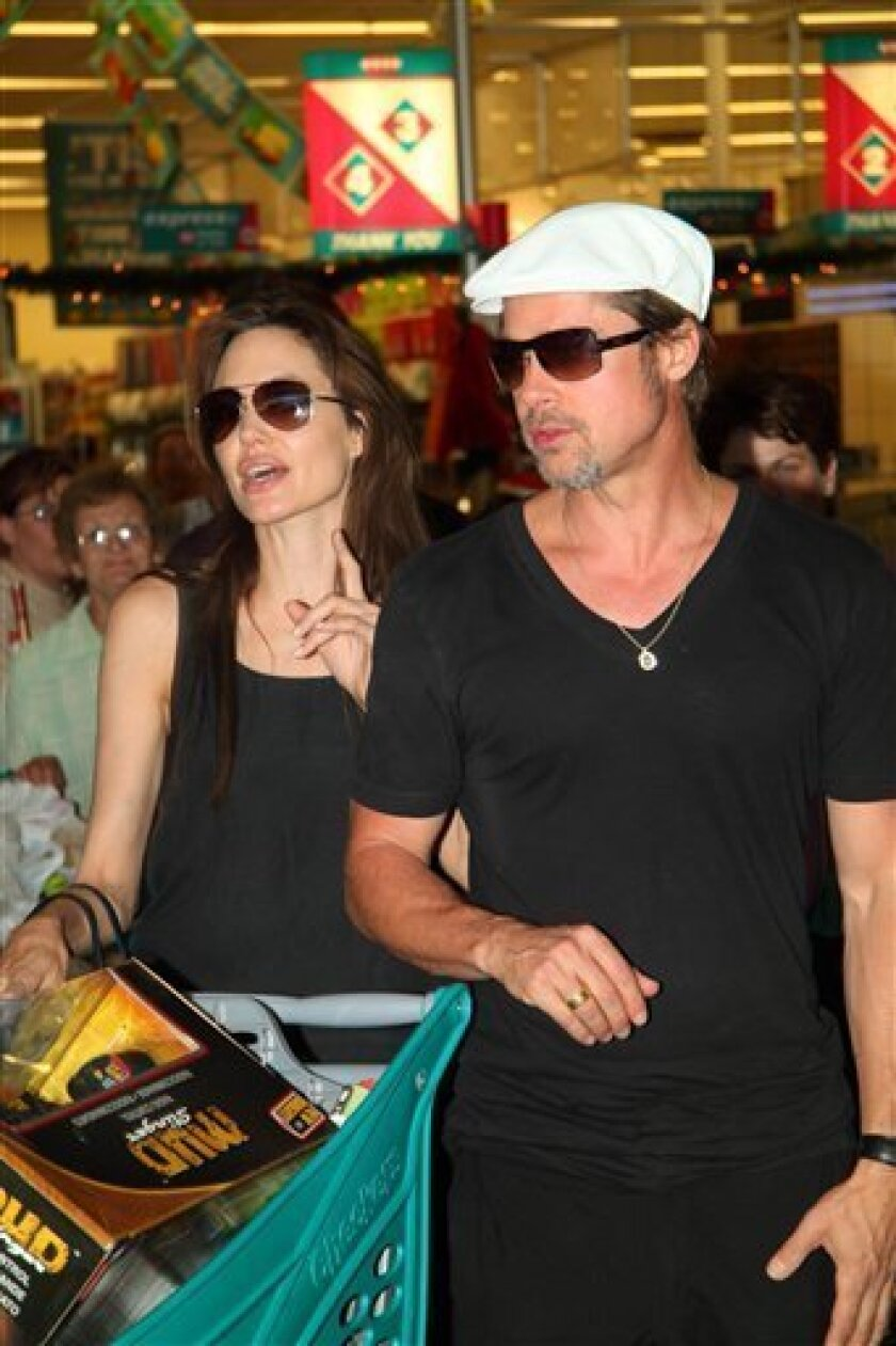 In this photo taken Thursday, Dec. 23, 2010 Angelina Jolie and Brad Pitt do Christmas shopping at a mall in Windhoek, Namibia . Jolie gave birth to twins two years ago in Nice, France. (AP Photo/Francois Poolman)