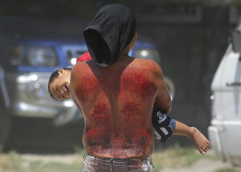 A hooded Filipino penitent plays with his son after his flaggelation during Good Friday rituals to atone for sins on April 3, 2015 in Pampanga province, northern Philippines. The bizarre ritual is frowned upon by church leaders in this predominantly Roman Catholic country. (AP Photo/Aaron Favila)