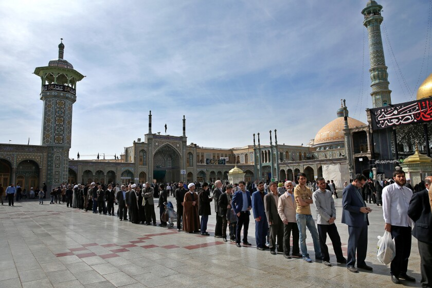 Iranians stand in line outside a polling station during the parliamentary and Experts Assembly elections in Qom on Friday.