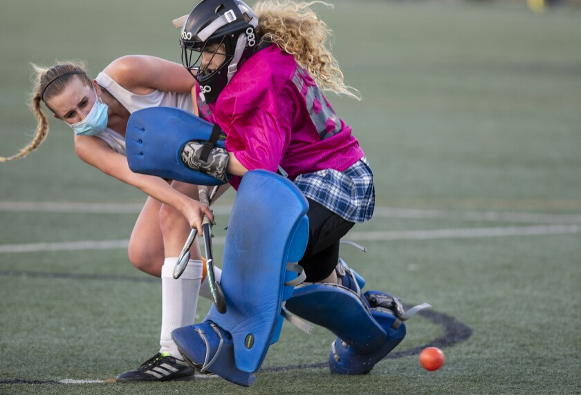 Huntington Beach's Taylor Rubly shoots and scores as Newport Harbor's Cadence Cockrell challenges her.