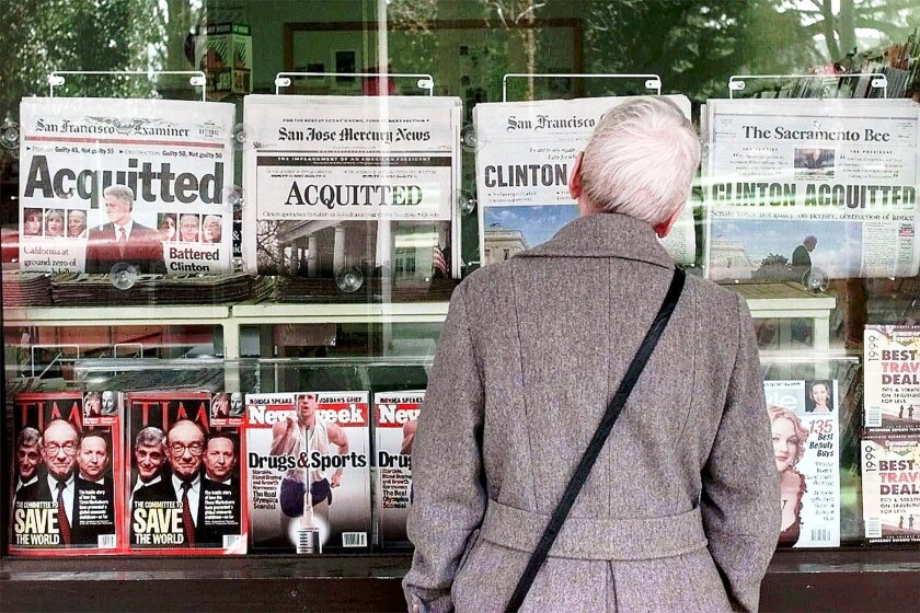 Feb. 13, 1999: A woman in Sacramento looks at newspaper headlines announcing the acquittal of President Bill Clinton.