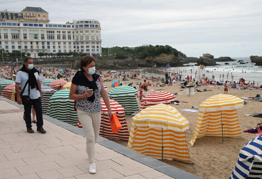 FILE - In this Wednesday, July 28, 2021 file photo, people wear face masks, to protect against coronavirus, walk on the pedestrian promenade along the beach in Biarritz, southwestern France. The majority of families with low income living in the European Union, the world's largest economy, can't afford a summer holiday, according to a study by the the European Trade Union Confederation (ETUC) released on Monday, Aug. 2, 2021. (AP Photo/Bob Edme, File)