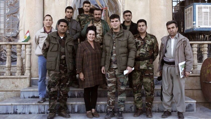 """Kelly Galindo with Kurdish soldiers while filming her documentary, """"26 Seconds,"""" in Iraq. The commander of the group assigned soldiers to watch over Galindo as she filmed for her documentary on child trafficking."""