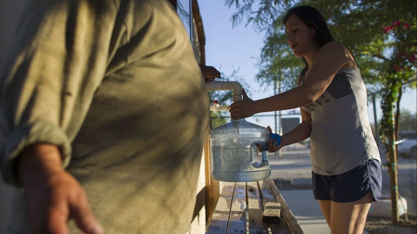 MECCA, CA - SEPTEMBER 23, 2015: Jorge Granados,left, helps a resident fill a container with filtered