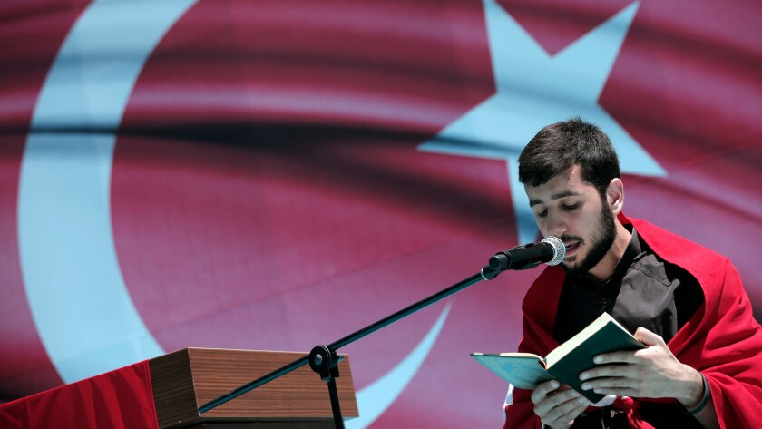 A youth recites from the Quran, Islam's Holy Book, during a pro-government protest against the attempted coup, in Istanbul, Turkey on July 19.