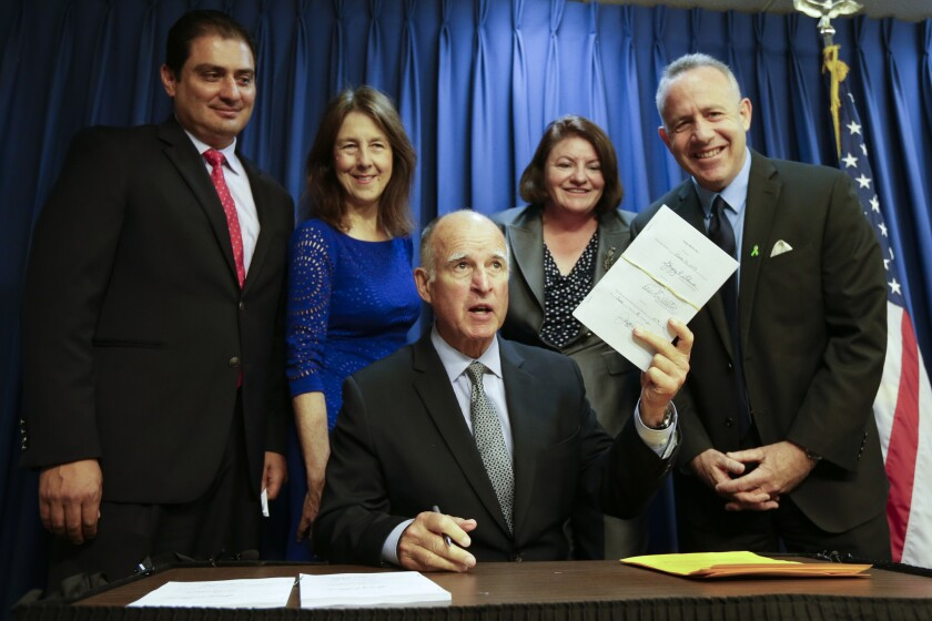 California's finances have improved enough to receive a credit upgrade from Moody's, a Wall Street ratings agency. Gov. Jerry Brown, pictured here with state lawmakers, signed a new budget into law last week.