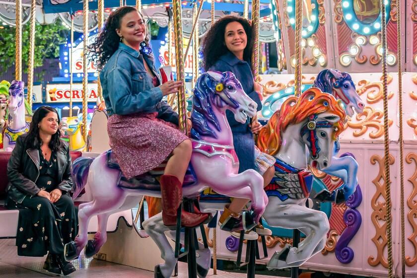 Three women ride on a carousel