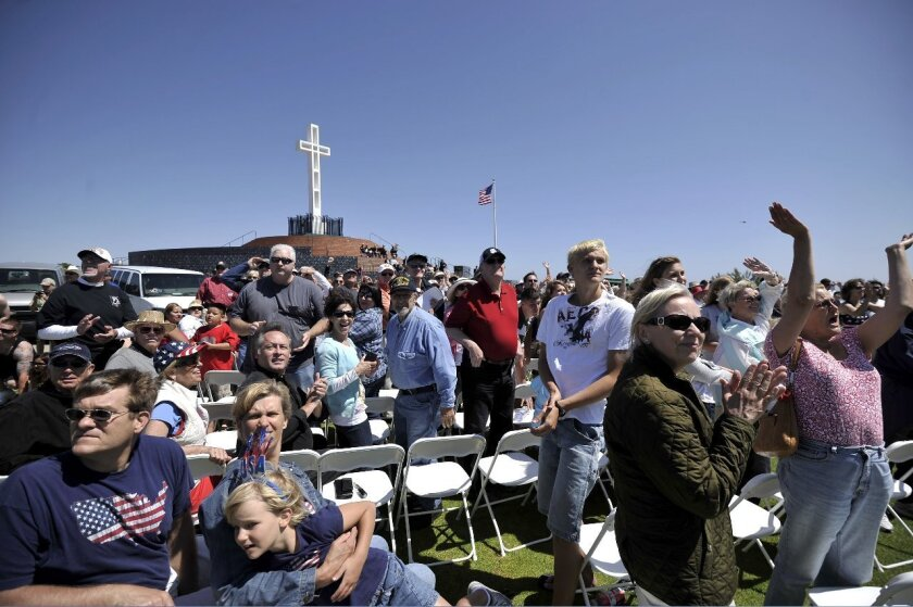 The crowd at the Mt. Soledad Veterans Memorial claps as a squadron of airplanes flies overhead in the missing man formation. Photo: Jerod Harris
