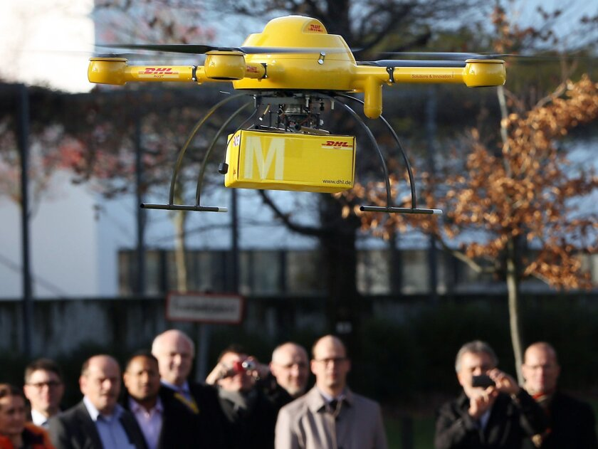 A drone with a small parcel flies in front of journalists in Bonn Germany, Monday Dec. 9, 2013. Germany's express delivery and mail company Deutsche Post DHL is testing a drone that could be used to deliver urgently needed goods to hard-to-reach places. The small pilotless helicopter was to fly a package of medicine Monday from a pharmacy in the town of Bonn to the company's headquarters on the other side of the Rhine River. The aircraft can carry up to 3 kilograms (6.6 pounds). (AP Photo/dpa,Oliver Berg)