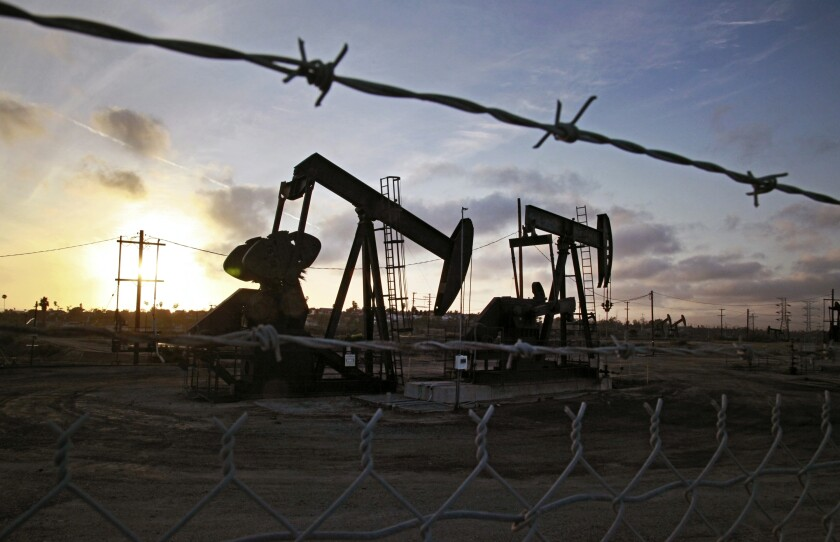 The sun sets beyond pumpjacks operating at the Inglewood oil fields in Baldwin Hills.