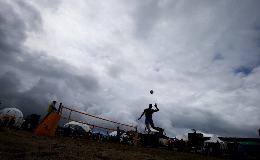 A beach volleyball player leaps to make a serve under stormy skies during the AVP Huntington Beach Open.