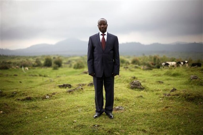FILE - In this Dec. 5, 2012 file photo, Congolese M23 rebel president Jean-Marie Runiga poses for a portrait at his hideout near the Congo-Uganda border town of Bunagana. The rebel group starting negotiations with the Congolese government wants the country's president to resign, according to a rebel document shown to The Associated Press on Thursday, Dec. 13, 2012 by Jean-Marie Runiga, president of the M23 rebels. (AP Photo/Jerome Delay, File)