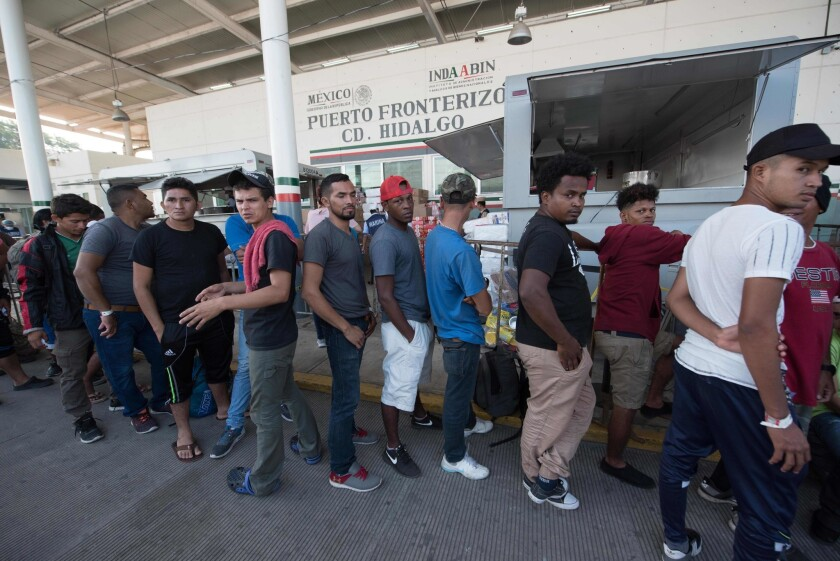 Central American migrants heading to the United States wait for immigration officials to give them a humanitarian visitor card to continue on their journey, in Ciudad Hidalgo, Mexico.