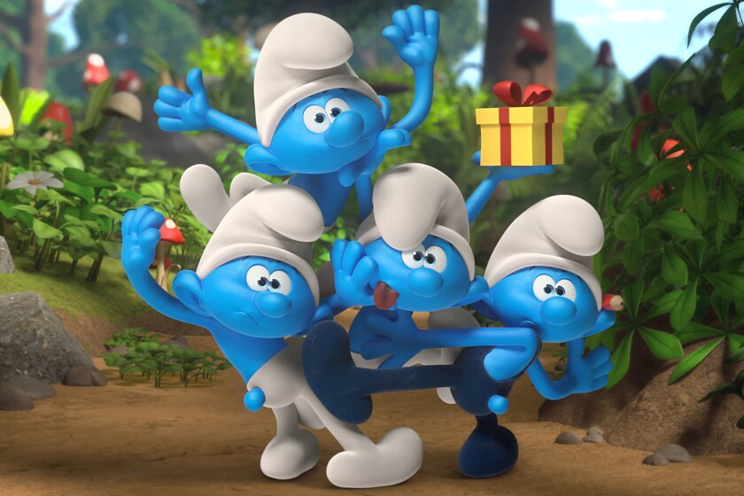 Four Smurfs in a clearing, one holding a wrapped present.