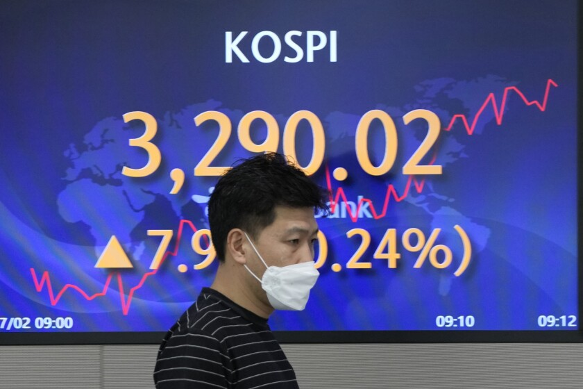A currency trader walks near a screen showing the Korea Composite Stock Price Index (KOSPI) at a foreign exchange dealing room in Seoul, South Korea, Friday, July 2, 2021. Shares were mostly higher in Asia on Friday, though markets in Shanghai and Hong Kong declined a day after the Chinese Communist Party marked its centenary with tough talk by Chinese President Xi Jinping. (AP Photo/Lee Jin-man)