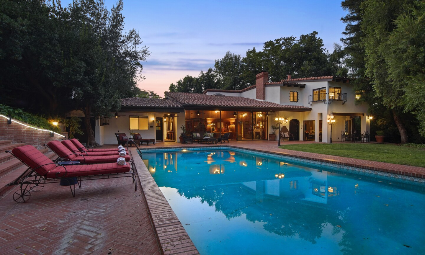 The half-acre property holds four residences, a swimming pool, gym and lawn lined with lampposts.