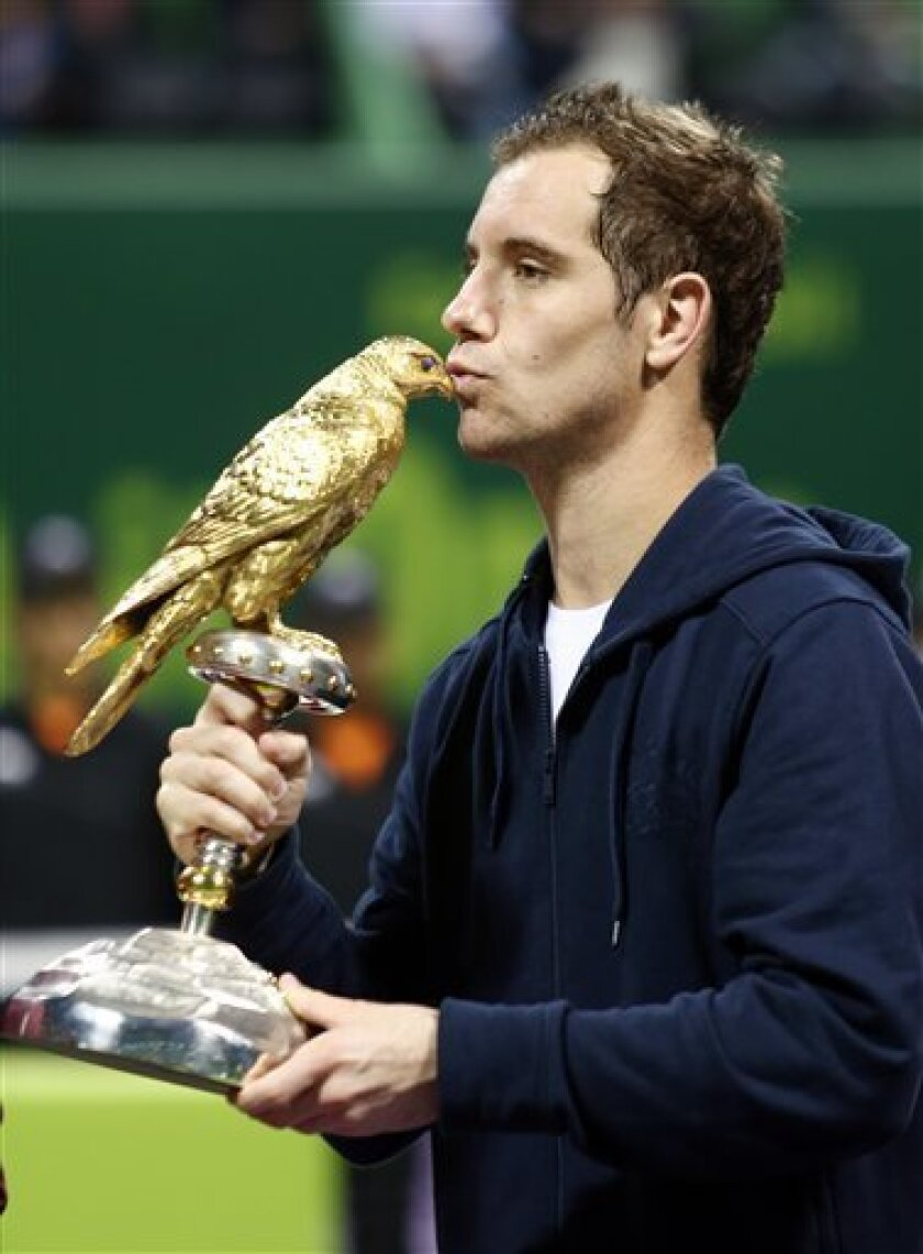 Richard Gasquet of France poses with the trophy after winning the final match against Nikolay Davydenko of Russia during the ExxonMobil Qatar ATP Open Tennis tournament at the Khalifa Tennis Squash Complex in Doha, Qatar, Saturday, Jan. 5, 2013. (AP Photo/Osama Faisal)