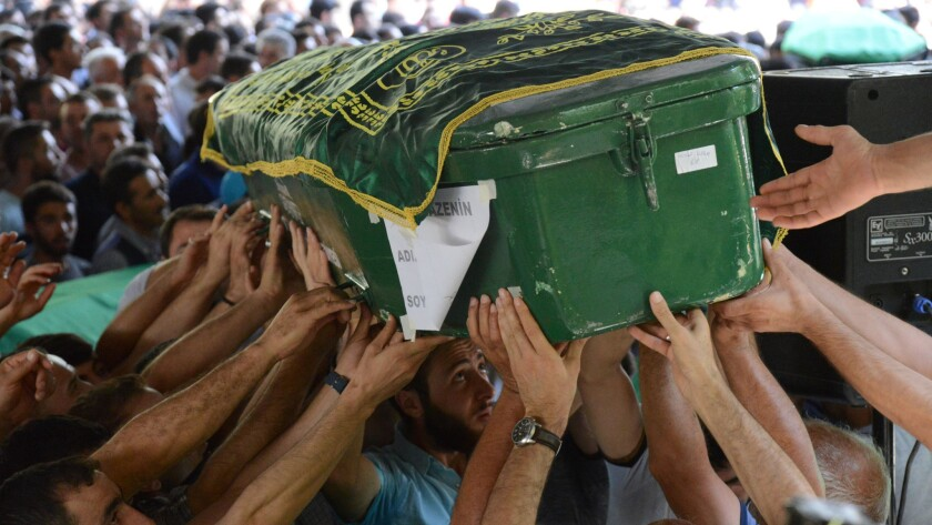People carry the coffin of a bombing victim during a funeral Sunday, after an attack on a wedding party left at least 51 dead in Gaziantep, in southeastern Turkey, near the Syrian border.