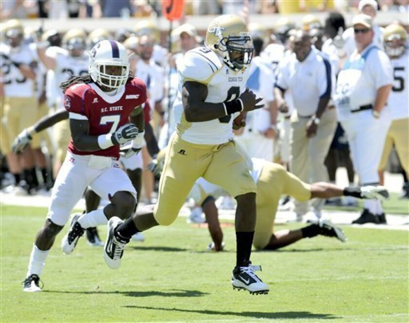 Georgia Tech quarterback Joshua Nesbitt, right, breaks loose and runs for the ends zone to score a touchdown as South Carolina State's Dominique Ellis (7) cheses during the first quarter of an NCAA college football game at Bobby Dodd Stadium Saturday, Sept. 4, 2010 in Atlanta. (AP Photo/Gregory Smith)