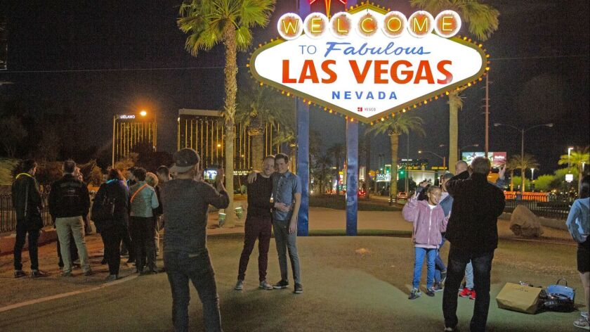 People pose for pictures at the iconic Las Vegas sign at all hours of the day or night.