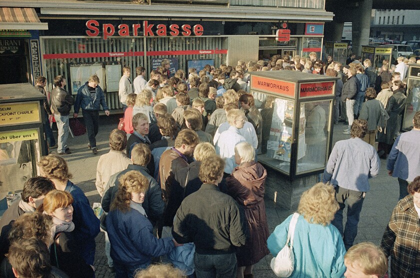 """FILE - In this Nov. 10, 1989, file photo East Berliners queue outside a West Berlin bank to receive the 100-Deutsche-Mark """"welcome money"""" the West German government gives all East Germans as financial help. The abrupt fall of the Wall in 1989 and lightning speed that reunification took place took everyone by surprise at the time and was a shock to the system for some 16 million East Germans. Unrealistic expectations combined with other factors have helped lead to today's discontent, providing fertile ground for the far-right. (AP Photo/Udo Weitz, File)"""