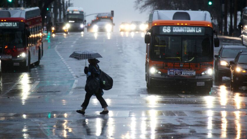 A pedestrian crosses a downtown Los Angeles street on a rainy Friday in January.