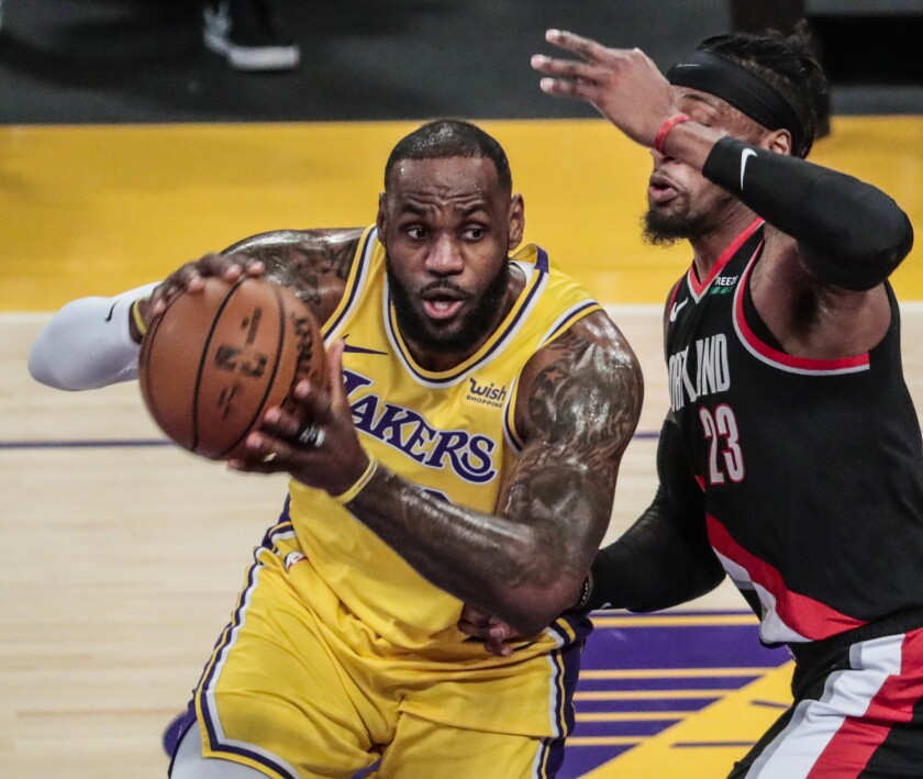 Lakers forward LeBron James looks to pass while covered by Portland Trail Blazers forward Robert Covington.