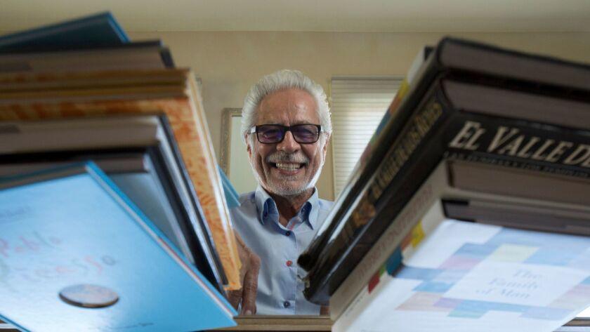 Rueben Martinez, surrounded by books.