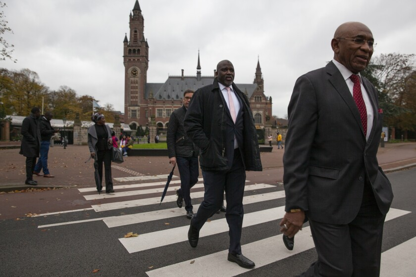 """Gambia's Justice Minister Aboubacarr Tambadou, center, and his delegation leave the Peace Palace, rear, which houses the International Court in The Hague, Netherlands, Monday, Nov. 11, 2019, after filing a case at the United Nations' highest court accusing Myanmar of genocide in its campaign against the Rohingya Muslim minority. A statement released Monday by lawyers for Gambia says the case also asks the International Court of Justice to order measures """"to stop Myanmar's genocidal conduct immediately."""" (AP Photo/Peter Dejong)"""