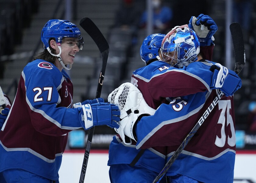 Colorado Avalanche left wing Gabriel Landeskog (92) celebrates with goaltender Jonas Johansson (35) and Ryan Graves (27) after the teams win against the Los Angeles Kings to clinch the President's Cup following an NHL hockey game Thursday, May, 13, 2021, in Denver. (AP Photo/Jack Dempsey)