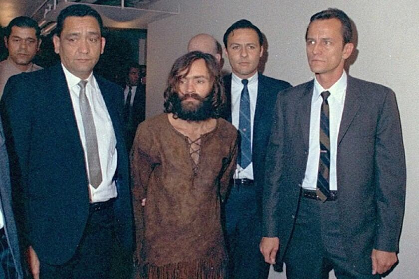 Charles Manson, escorted by three men in suits.