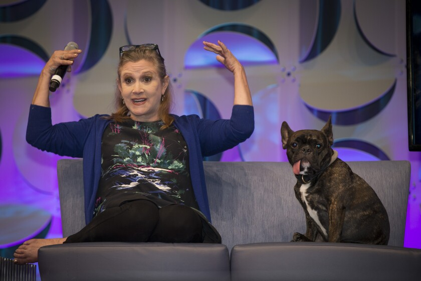 """""""Star Wars"""" actress Carrie Fisher, joined by her dog Gary, talks onstage during her presentation at Star Wars Celebration on April 17 at the Anaheim Convention Center."""