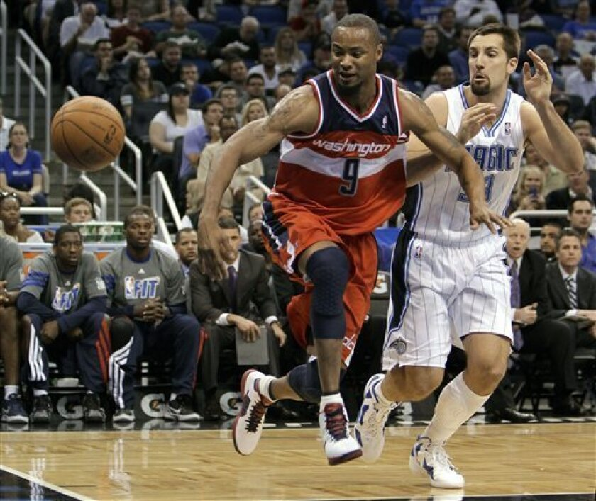 Washington Wizards' Rashard Lewis (9) loses control of the ball as he tries to drive past Orlando Magic's Ryan Anderson during the first half of an NBA basketball game Wednesday, Feb. 1, 2012, in Orlando, Fla. (AP Photo/John Raoux)