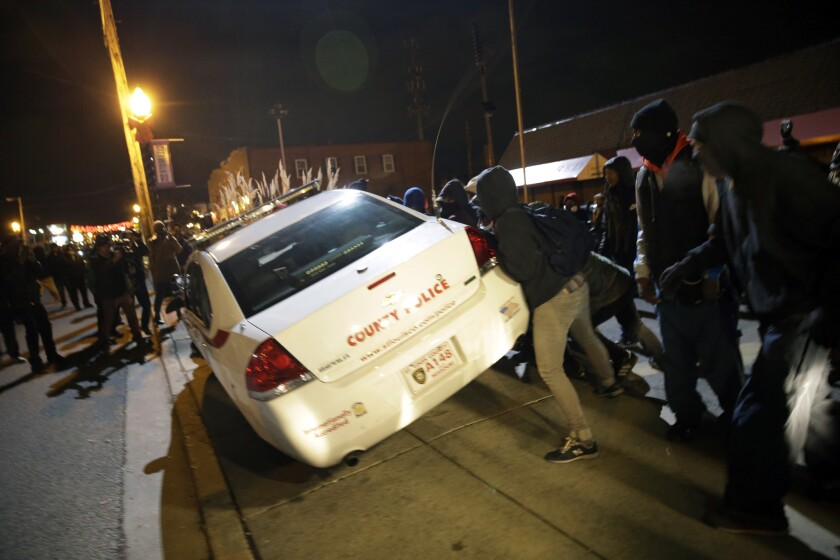 Protesters in Ferguson, Mo., shove a police car after the announcement of the grand jury decision not to indict police Officer Darren Wilson in the fatal shooting of Michael Brown, an unarmed black 18-year-old.