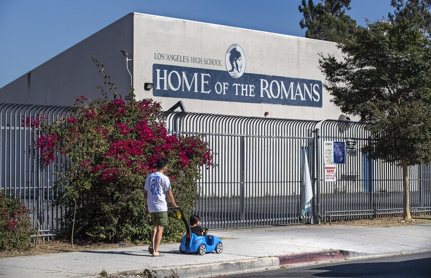 Kenzo Bergeron, 40, and his son Coyne, 2, make their way past Los Angeles High School on July 13.