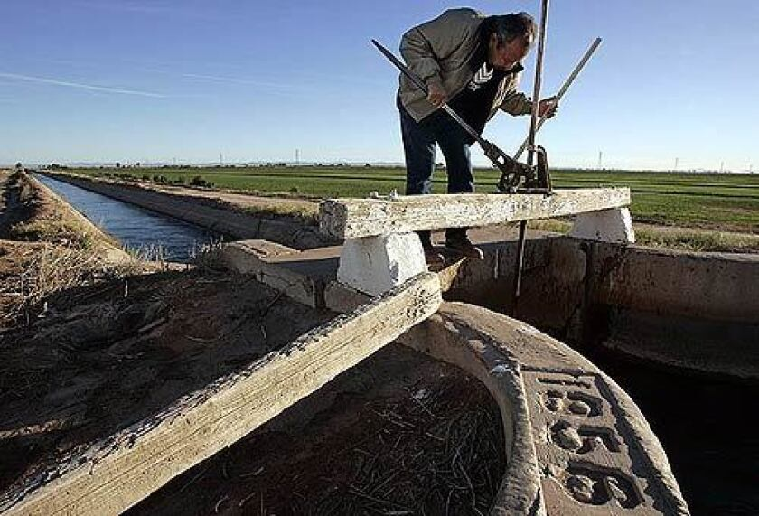 Jose Romo, a zanjero with the Imperial Irrigation District, uses a metal jack to open a gate that controls the release of water into ditches for crops in the Imperial Valley.