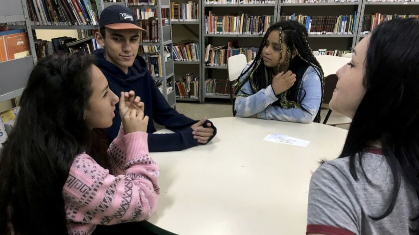 Evelyn Ruama Martins Trindade, 16, from left; Joao Pedro Moreira de Souza, 15; Monalisa Dantas, 16; and Jessica Nunes de Carvalho, 15, in the library of the Professora Cynira Pires dos Santos public school.