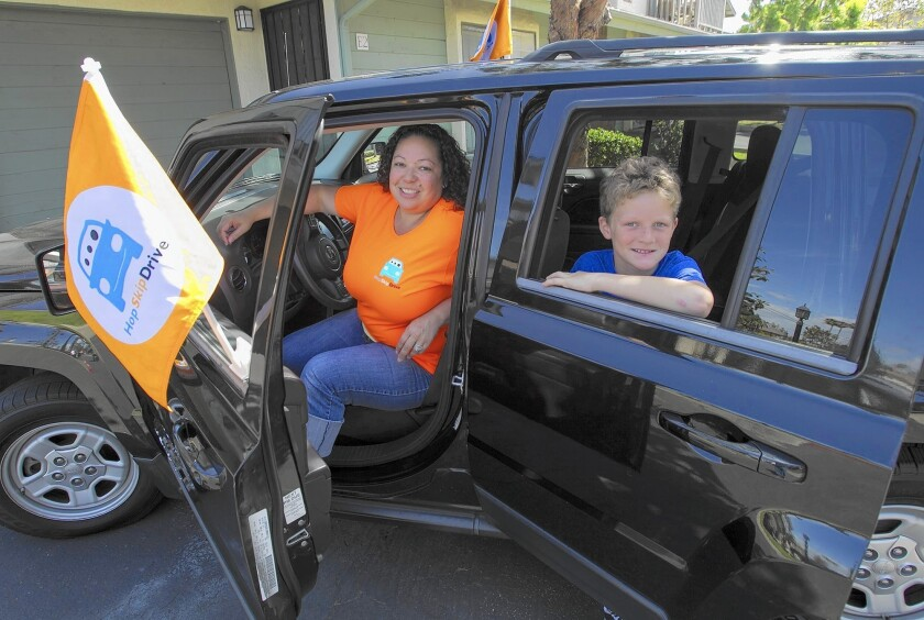 Costa Mesa resident Leah Fountain, left, is a new CareDriver with HopSkipDrive, a transportation service geared for children that officially launches in Orange County in April. In the backseat is Cooper Dwight, 12.
