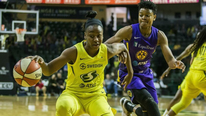 Seattle Storm's Jewell Loyd tries to get around Los Angeles Sparks' Alana Beard during a WNBA basket