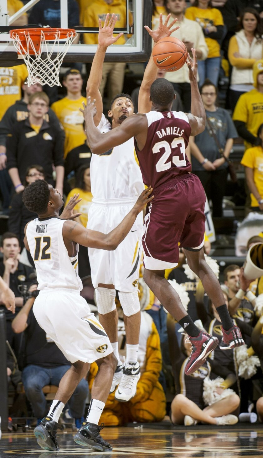 Mississippi State's Travis Daniels, right, has his shot blocked by Missouri's Johnathan Williams III, center, as Missouri's Namon Wright, left, looks on during the first half of an NCAA college basketball game Saturday, Feb. 14, 2015, in Columbia, Mo. (AP Photo/L.G. Patterson)