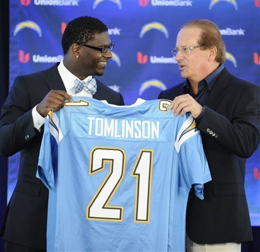 Former San Diego Chargers running back LaDainian Tomlinson, left, and Chargers president Dean Spanos hold up Tomlinson's #21 jersey at a news conference held at the San Diego Chargers facility Monday, June 18, 2012 in San Diego.  The news conference was held so that Tomlinson could re-sign with the