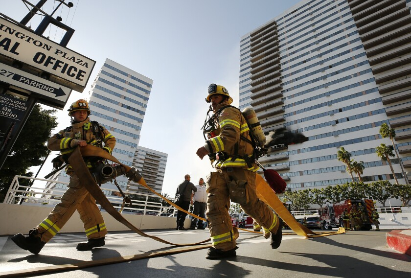 Firefighters carrying hoses on their way to fight a blaze at Barrington Plaza on Wilshire Boulevard on the city's Westside.