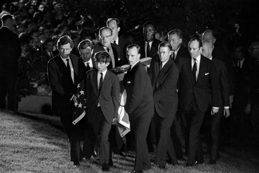 Men and one boy, wearing suits, carry a flag-draped coffin.